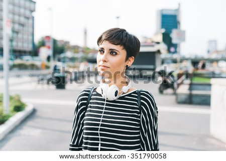 Half length of young handsome caucasian brown straight hair woman with headphones around her neck walking in the city, overlooking right, pensive - thoughtful, music concept - stock photo