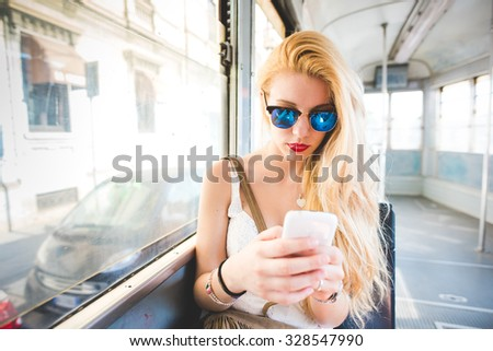 Half length of young handsome caucasian long blonde straight hair woman sitting on a bus, using smartphone, looking downward and tapping the screen - technology, social network, communication concept