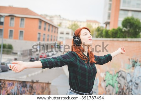Half length of young handsome caucasian redhead straight hair woman listening music with headphones, feeling free with eyes closed and arms wide open - freedom, music, carefree concept - stock photo