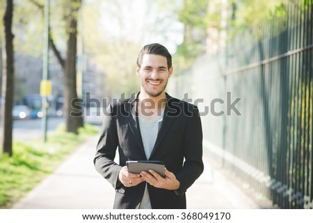 Half length of young handsome italian boy walking through the city using a tablet handhold connected online looking in camera smiling - technology, social network concept - stock photo