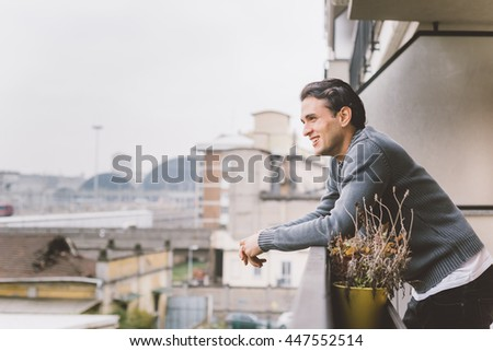 Half length of young handsome man standing on a balcony outdoor, overlooking, happy - positive, carefree, thinking future concept - stock photo