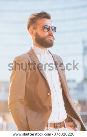 Half length of young handsome modern businessman wearing sunglasses, posing in the city backlight, overlooking right - business, success concept - stock photo