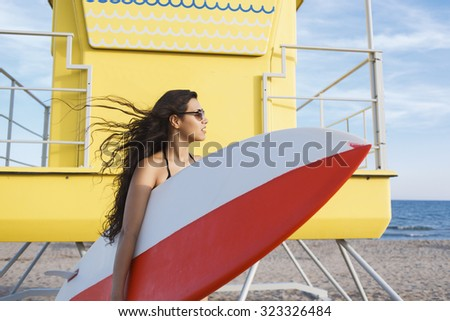 Half length portrait of a charming Latin women holding surfing board with copy space for your brand, young female waiting on the beach her friends for surfing together during summer vacations  - stock photo