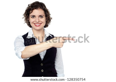 Half length portrait of a confident employee pointing towards her left. - stock photo