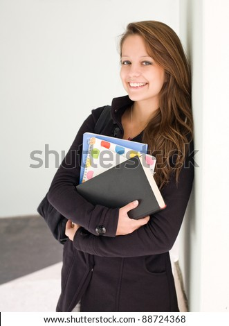 Half length portrait of a cute young smiling student with exercise books.