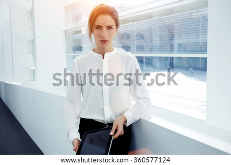 Half length portrait of a female managing director posing with touch pad in hands while standing in office interior, confident smart businesswoman resting after work on digital tablet during break - stock photo