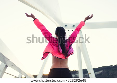 Half length portrait of a fit woman dressed in colorful windbreakers standing with raised hands while relaxing after workout out, female runner enjoying beautiful day and rest after fitness training - stock photo