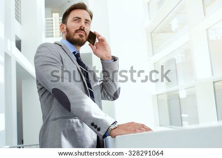 Half length portrait of a intelligent man lawyer calling with cell telephone while standing in modern office space, young confident male entrepreneur speaking on smart phone while rest after meeting   - stock photo