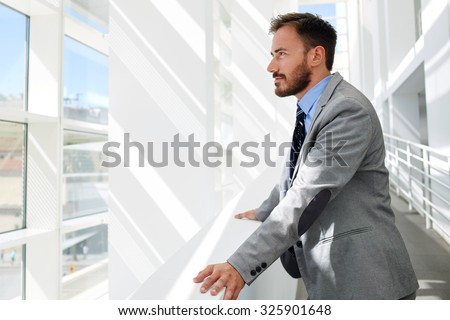 Half length portrait of a men dressed in luxury elegant clothes watching in window while standing in modern space, thoughtful successful businessman in suit resting after meeting with his partners - stock photo