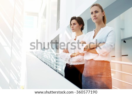 Half length portrait of a two female rivals with crossed arms standing side by side in office interior, team of skilled women partners of the company dissatisfied with the result of important meeting - stock photo