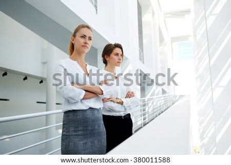 Half length portrait of a two successful financiers with serious look posing in modern office interior, team of female leaders ponders over the future of company during work break in office hallway - stock photo