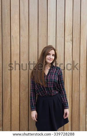 Half length portrait of a young beautiful hipster girl dressed in stylish clothes posing outdoors against wooden wall, charming Caucasian woman with pretty face standing on copy space area background - stock photo