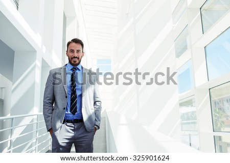 Half length portrait of a young smiling businessman dressed in corporate clothing with hands in pockets standing in modern space, handsome happy intelligent man in luxury suit relaxing after work day  - stock photo