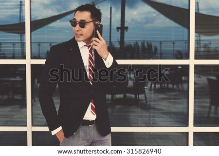 Half length portrait of a young successful asian businessman in formal wear calling with smart phone during work break, stylish men entrepreneur talk on mobile phone while standing near office window - stock photo