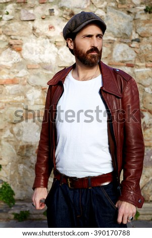 Half length portrait of adult man dressed in white casual shirt with mock up copy space for advertise text,bearded hipster guy in fashion clothes is looking away while standing outdoors in sparing day - stock photo