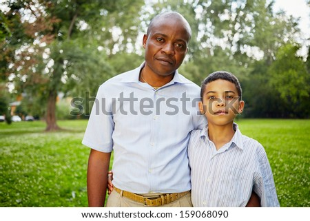 Half-length portrait of african father and son in summer park
