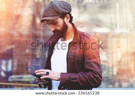 Half length portrait of an adult bearded hipster man chatting on mobile phone while standing in urban setting, handsome male tourist dressed in stylish clothes using cell telephone for navigation  - stock photo