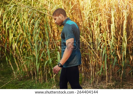 Half length portrait of athletic dark-skinned man having a rest after workout while walking outdoors, muscular build young runner training in beautiful park, relaxing athlete having break - stock photo