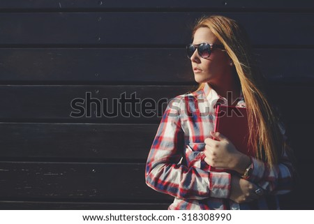 Half length portrait of attractive hipster girl with a pink notebook in hands standing on a wooden wall background outdoors, young teenager in sunglasses posing against copy space area for content - stock photo