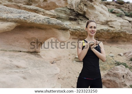Half length portrait of attractive sportive woman warming up before began her fitness training outdoors in mountain landscape,young female runner doing wrist exercise, copy space area for text message - stock photo