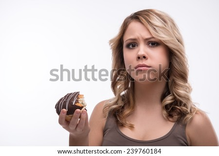 Half-length portrait of attractive worried blonde woman biting doughnut, weight loss concept, isolated on white background, selective focus - stock photo