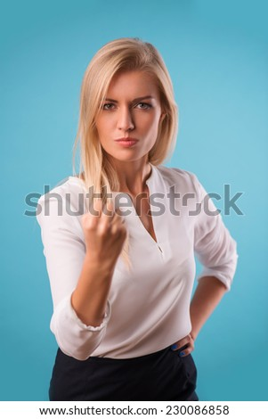 Half-length portrait of beautiful angry blonde wearing white classic blouse and black skirt standing threatening us. Isolated on blue background - stock photo