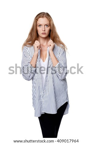 Half length portrait of beautiful blond female fashion model posing in plaid striped shirt over white background - stock photo
