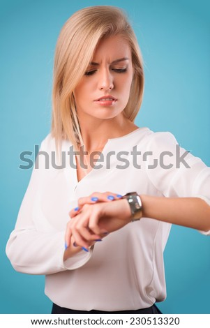 Half-length portrait of beautiful business lady wearing white classic blouse and black skirt looking at her watch thinking about the meeting today. Isolated on blue background - stock photo