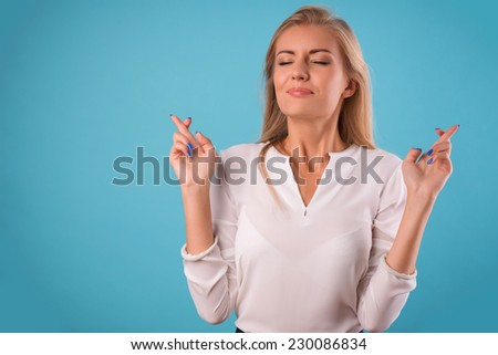 Half-length portrait of beautiful dreamy blonde wearing white classic blouse and black skirt standing crossing her fingers with closed eyes wanted to make her wishes come true. Isolated on blue - stock photo