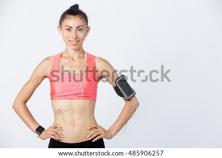 Half-length portrait of beautiful happy young person wearing armband and red sportswear top posing. Smiling sporty model girl with perfect body working out, listening music. Studio image. Copy space