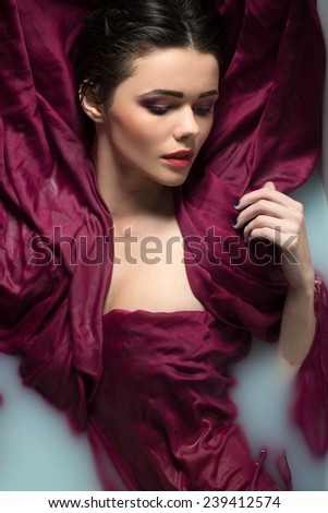 Half-length portrait of beautiful sexy dark-haired woman closing her eyes lying in the bath covering herself with the wine-colored cloth looking dreaming about something - stock photo