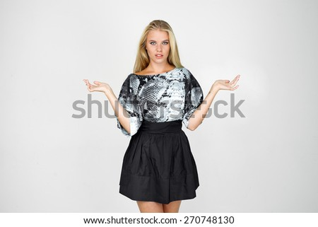 Half-length portrait of beautiful smiling blonde wearing blouse and black skirt standing aside pointing out something looking at us. Isolated on gray background - stock photo