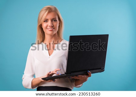 Half-length portrait of beautiful smiling business lady wearing white classic blouse and black skirt standing looking at us holding the laptop. Isolated on blue background - stock photo