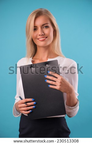 Half-length portrait of beautiful smiling business lady wearing white classic blouse standing aside looking at us holding in her hands the black folder. Isolated on blue background - stock photo