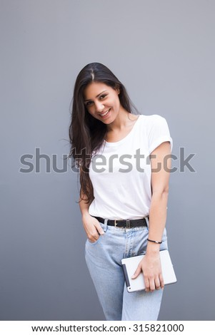 Half length portrait of beautiful smiling latin woman holding her digital tablet computer while posing for the camera against street wall, happy pretty female with touch pad in hand looking at you - stock photo