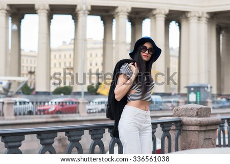 Half length portrait of beautiful woman leaning on bridge fence and looking at the camera, young and elegant model is posing on the background of urban setting while chilling after evening excursion  - stock photo