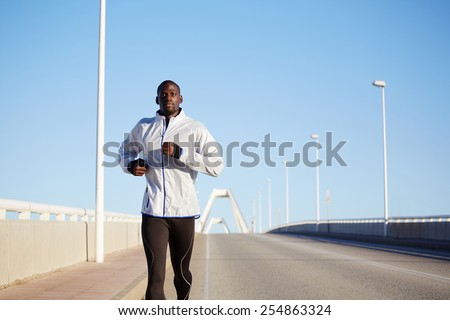Half length portrait of black sportive man running on beautiful road over blue sky background - stock photo