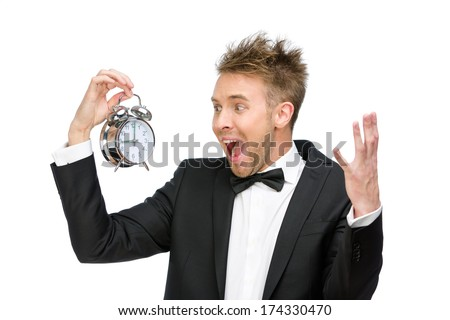 Half-length portrait of businessman looking at alarm clock and shouting, isolated on white