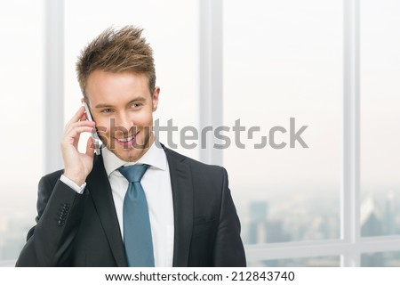 Half-length portrait of businessman speaking on cell phone against window with urban view. Concept of communication and business - stock photo