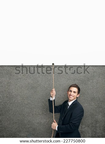 Half-length portrait of businessman swarming up the string with white poster, isolated on white. Concept of job promotion and hard work. Copyspace - stock photo