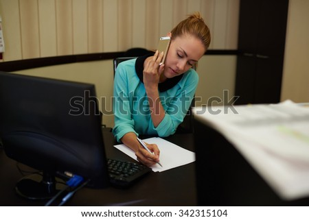 Half length portrait of busy young woman signing papers at comfortable office table and talking on mobile phone, modern business lady in corporate clothing working at her workplace on smart devices  - stock photo