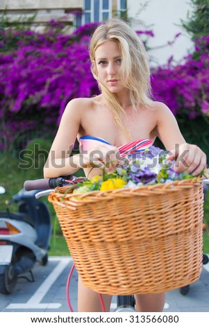 Half length portrait of charming hipster girl leaning on her retro bike with a basket of summer flowers resting after riding in the city, cute blonde female strolling with classic bicycle in the park - stock photo