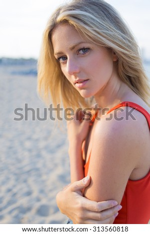 Half length portrait of charming woman with pretty face standing on the beach at summer sunny afternoon, beautiful caucasian female posing for the camera while looking at you, Sweden model - stock photo