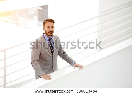 Half length portrait of confident male business owner standing in office building inside during work day, elegant man employee dressed in luxury suit posing in modern hallway of his big company - stock photo