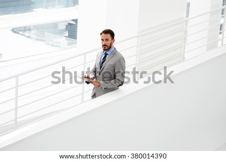 Half length portrait of confident man entrepreneur searching information on touch pad while standing in office interior, intelligent male manager checking e-mail on digital tablet during work break - stock photo