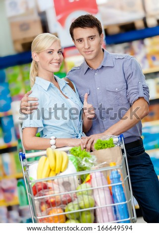 Half-length portrait of couple in the market with cart full of food. Concept of consumerism and healthy food - stock photo