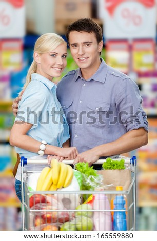 Half-length portrait of couple in the supermarket with cart full of food. Concept of consumerism and healthy food - stock photo