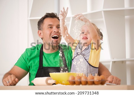 Half-length portrait of cute little daughter with happy handsome father cooking pastry, mixing flour. Eggs, bowl and roller pin - stock photo