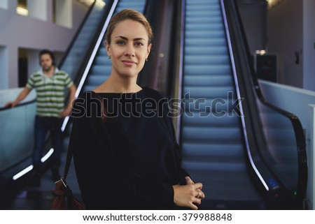 Half length portrait of elegant woman entrepreneur posing near escalator in airport while waiting for airplane, pretty young female with bags standing near moving stairs in shopping center interior