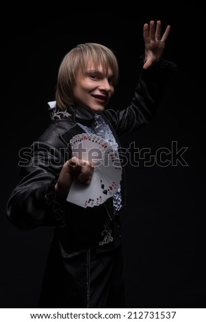 Half-length portrait of fair-haired matchless smiling juggler wearing interesting black costume and white shirt standing aside showing us different tricks with cards. Isolated on black background